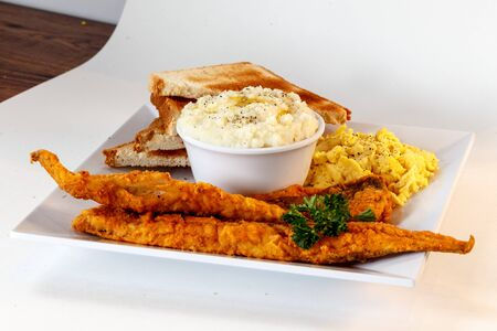 breakfast with fried fish, eggs and toast Imagens