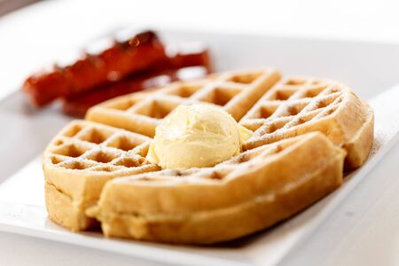 belgian waffle on plate with butter and sausage