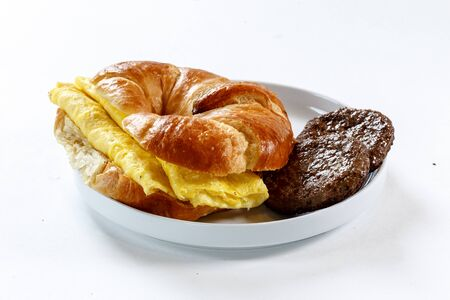 breakfast sandwich on croissant with egg and sausage Фото со стока - 83785387
