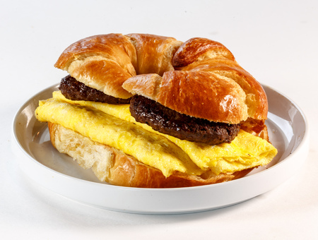 breakfast sandwich on croissant with sausage and egg 版權商用圖片