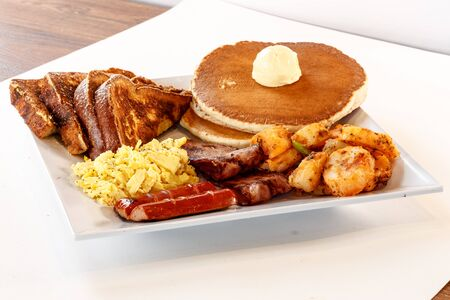 big breakfast with pancakes, sausage, eggs and potatoes