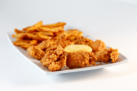 Chicken nuggets with sauce and french fries Фото со стока