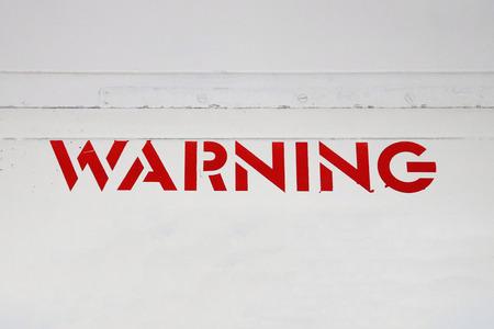 Red WARNING Sign on White Metal