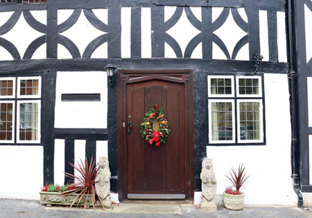Close up of Brown Door with Christmas Wreath on Traditional Black and White Tudor Style House