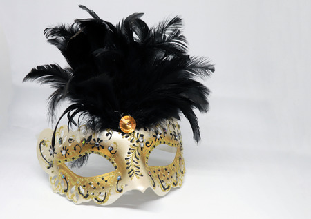 Closeup of Gold and Black Masquerade Fancy Dress Mask with Feathers Isolated on White Background