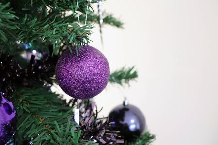 Closeup of Purple Sparkly Bauble Hanging on Christmas Tree