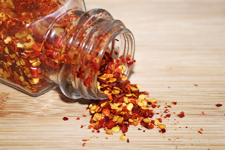 Chilli Flakes Spilling Out of Glass Jar on Wooden Chopping Board Imagens