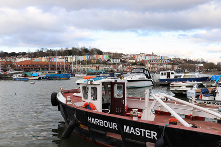 Harbourside Scene with Harbour Master Boat in Foreground and Colourful Houses in Background, Bristol, UK 에디토리얼