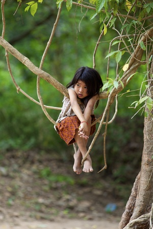 Siem Reap, Cambodia- April 1, 2011: Unidentified child plays in jungle at Ta Prohm Temple in Siem Reap, Cambodia on April 1, 2011 Stock Photo - 10379306