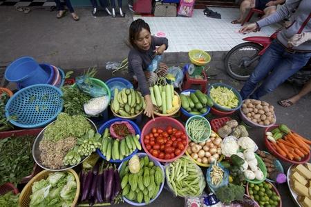 Ho Chi Minh City, Vietnam-Circa juni 2010: straatventer in Ho Tsji Minhstad, Vietnam verkoop van groenten op de stoep Redactioneel