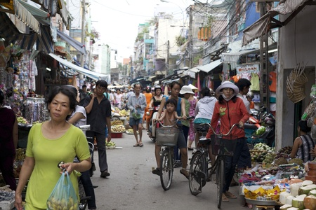 chi: Ho Chi Minh City, Vietnam - May 23, 2010: Crowded marketplace with street vendor in Ho Chi Minh City, Vietnam selling produce and wares on the sidewalk