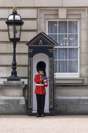 Londen - 21 juni 2009: Sentry van de Grenadier Guards geplaatst buitenkant van Buckingham Palace op 21 juni 2009 in Londen, Verenigd Koninkrijk. De Grenadier Guards sporen zijn afstamming terug tot het jaar 1656.