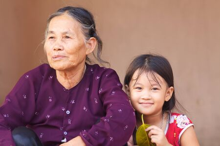 Duong Lam Village, Vietnam- Sept 3, 2010: An unidentified Vietnamese child sits with her grandmother on September 3, 2010 in Duong Lam Village, Vietnam Editorial