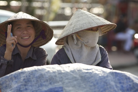 conical hat: Hai Phong, September 29, 2008: Unidentified Vietnamese women wearing traditional conical hat on September 29, 2008 in Hai Phong, Vietnam. The median age of population in Vietnam is 27.8 years old.