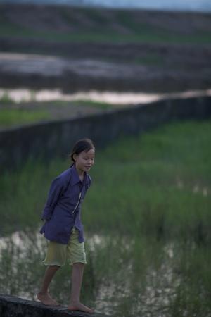 Hai Phong, Vietnam -Sept 29, 2008: Unidentified Vietnamese child walks along field in Hai Phong Vietnam on September 29, 2008. Vietnams 2011 population is 90,549,390 with 25% of the population under age 14