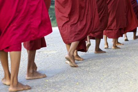 Een stoet van monniken op blote voeten lopen voor de ochtend aalmoezen in Bagan, Myanmar