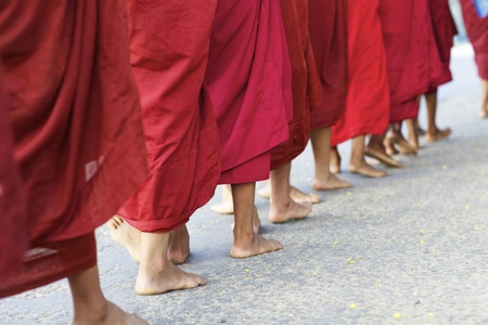 A procession of monks walking barefoot for morning alms in Bagan, Myanmar