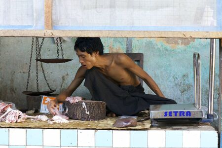 butchering: Nyaung-U, Myanmar - Oct 14, 2011: A butcher cutting up meat for sale in the market in Nyaung-U, Myanmar on October 14, 2011.