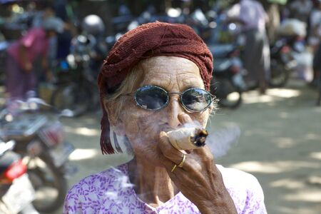 cheroot: Nyaung-U, Myanmar - October 14, 2011: An unidentified woman smoking a cheroot cigar in Nyaung-U, Myanmar on October 14, 2011.