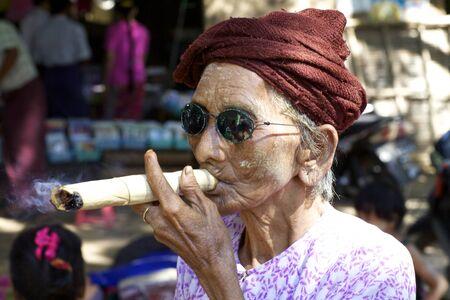 Nyaung-U, Myanmar - 14 oktober 2011: een niet geïdentificeerde vrouw roken van een sigaar sigaar in Nyaung-U, Myanmar op 14 oktober 2011