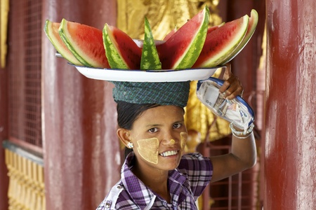 median age: Bagan, Myanmar - October 14, 2011: An unidentified woman selling watermelon in Bagan on Oct 14, 2011. Myanmar has a population of 53,999,804 people, with the median age being 26.9 years of age.