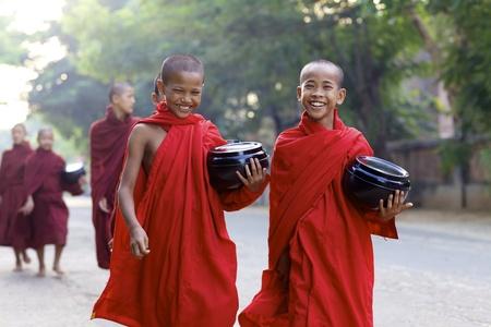 Old Bagan, Myanmar - 15 oktober 2011: Twee onbekende jonge beginnende monniken lopen ochtend aalmoezen in Old Bagan, Myanmar op 15 oktober 2011.