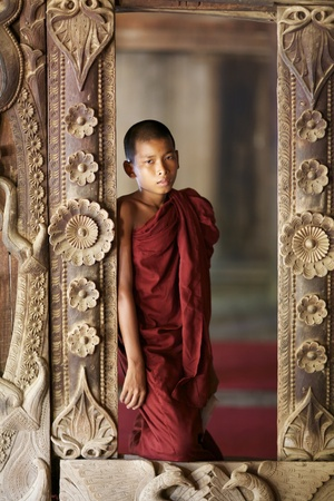 Old Bagan, Myanmar - October 15, 2011: An unidentified young novice monk standing in window in Old Bagan, Myanmar on October 15, 2011. 89% of the Burmese population is Buddhist. Stock Photo - 11117827