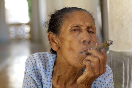 cheroot: Bagan, Myanmar - Oct 14: An unidentified woman smoking a cheroot cigar in Bagan, Myanmar on October 14, 2011.