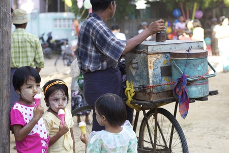 Bagan, Myanmar - Oct. 14: Three unidentified Burmese children eating ice cream from the local ice cream vendor with bicycle in Bagan, Myanmar on October 14, 2011.