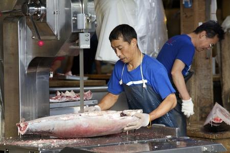 butchering: TOKYO - JULY 4: Workers processing Tuna at the Tsukiji Wholesale Seafood and Fish Market in Tokyo Japan on July 4, 2011. Tsukiji Market is the biggest wholesale fish and seafood market in the world.