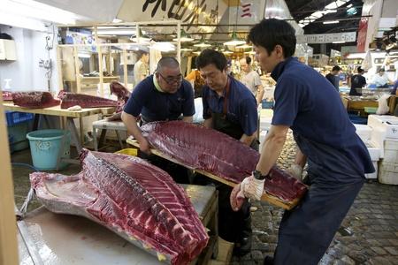 TOKYO-JULI 4: Arbeiders verwerking tonijn op de Tsukiji Wholesale Seafood en vismarkt in Tokyo Japan op 4 juli 2011. Tsukiji Market is de grootste groothandel vis en zeevruchten markt in de wereld.