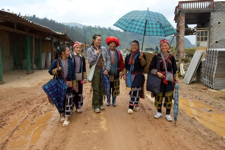 SAPA, VIETNAM - NOV 22: Unidentified women from the Red Dao Ethnic Minority People guide American tourist on November 22, 2010 in Sapa, Vietnam. Red Dao are the 9th largest ethnic group in Vietnam Stock Photo - 11390182
