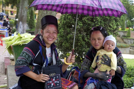 SAPA, VIETNAM - JULY 7: Unidentified women from the Black Hmong Ethnic Minority People hold a baby on July 7, 2007 in Sapa, Vietnam.
