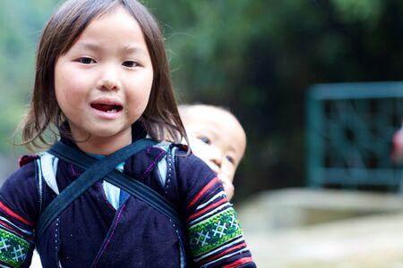 Sapa, Vietnam, NOVEMBER 22: Niet geïdentificeerd jong meisje van de Zwarte Hmong etnische minderheid mensen die baby in Sapa, Vietnam op 22 november 2010.