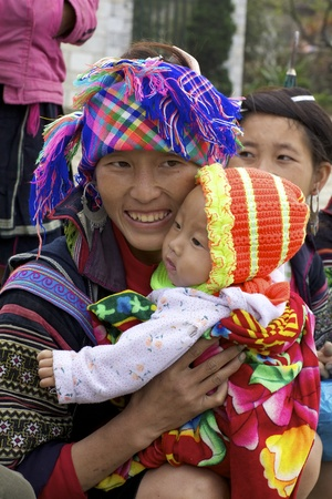 SAPA, VIETNAM - NOV 22: Unidentified girl from the Black Hmong Ethnic Minority People holding her baby on November 22, 2010 in Sapa, Vietnam.