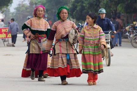 BAC HA, VIETNAM - NOV 21: Three women from the Flower Hmong Ethnic Minority People walk on November 21, 2010 in Bac Ha, Vietnam.  Stock Photo - 11390204