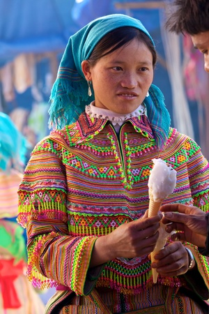 BAC HA, VIETNAM - NOV 21: Unidentified girl from the Flower Hmong Ethnic Minority People holds ice cream on November 21, 2010 in Bac Ha, Vietnam. Stock Photo - 11390220