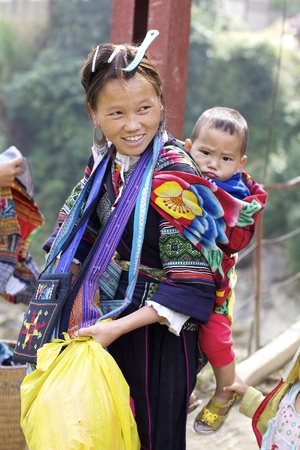 SAPA,VIETNAM - NOV 23: Unidentified girl of the Hmong Ethnic Minority carries baby on November 23, 2010 in Sapa, Vietnam.