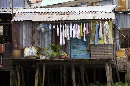 Can Tho, Vietnam-MEI 28: Een typisch shack huis langs de Mekong Delta met wasgoed drogen buiten in Can Tho, Vietnam op 28 mei 2011. Schatting 10,6% van de bevolking van Vietnam is onder de armoedegrens.