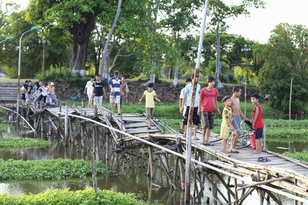 children pond: Hue, Vietnam - May 29: A group of kids walk across an old broken bridge in Hue, Vietnam on May 29, 2010