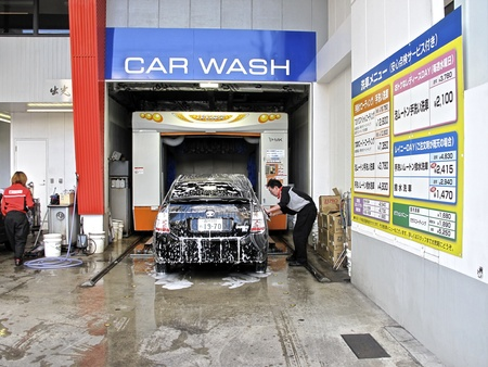 car wash: Tokyo, Japan - November 17, 2009: A worker cleans a vehicle at a downtown street side compact car wash in downtown Tokyo, Japan on November 17, 2009.