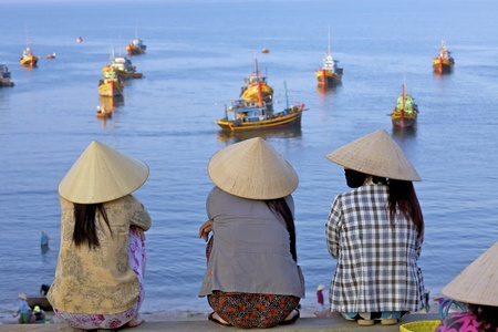 MUI NE, VIETNAM - APRIL 16: Unidentified women await returning fishing boats in Mui Ne, Vietnam at sunrise on April 16, 2011 Sajtókép