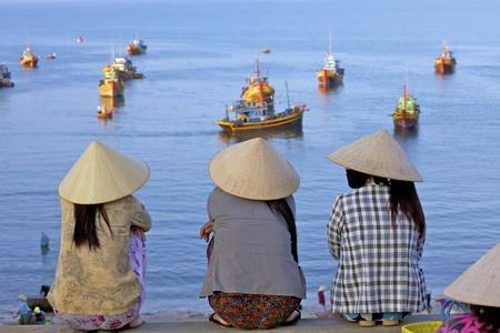 Mui Ne, Vietnam - 16 april: Unidentified vrouwen zie uit terugkerende vissersboten in Mui Ne, Vietnam bij zonsopgang op 16 april 2011
