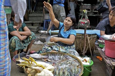 Yangon, Myanmar - 16 oktober: Een straat marktkoopman verkoopt kippen, garnalen en vis op de straten van Yangon, Myanmar op 16 oktober, 2011.