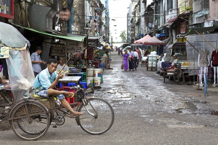 Yangon, Myanmar - Oct 16: A cyclo driver in the streets of Yangon, Myanmar on October 16, 2011.