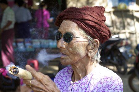 cheroot: NYAUNG-U, MYANMAR- OCT 14: An unidentified woman smoking a cheroot cigar in Nyaung-U, Myanmar on October 14, 2011.
