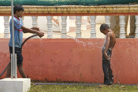 cool off: SIEM REAP, CAMBODIA- APRIL 1: Children play with a water house to cool off from the heat in Siem Reap, Cambodia on April 1, 2011