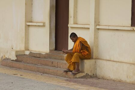SIEM REAP, CAMBODIA- APRIL 1: Unidentified Monk sits alone on steps in Siem Reap, Cambodia on April 1, 2011 Stock Photo - 11729471
