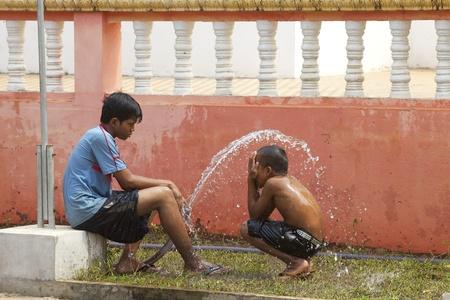 Siem Reap, Cambodja-APRIL 1: Kinderen spelen met een water-huis om af te koelen van de hitte in Siem Reap, Cambodja op 1 april 2011 Redactioneel