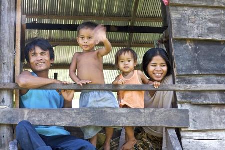 Siem Reap, Cambodja-okt 4: Een onbekend Cambodjaans echtpaar met hun kinderen te kijken vanuit hun huis in Siem Reap, Cambodja op 4 oktober 2008.